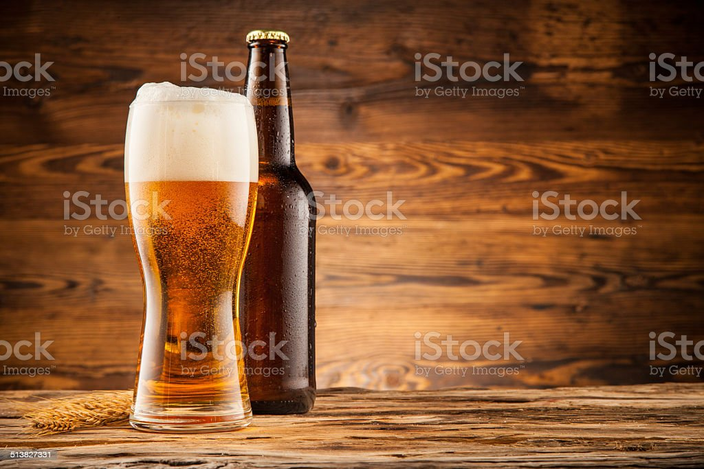 Glass and bottle of beer on wooden planks stock photo