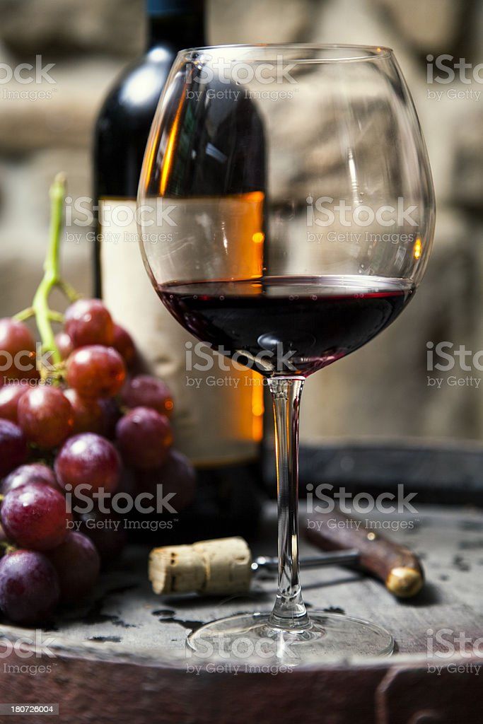 Glass and bottle of red wine in the cellar royalty-free stock photo