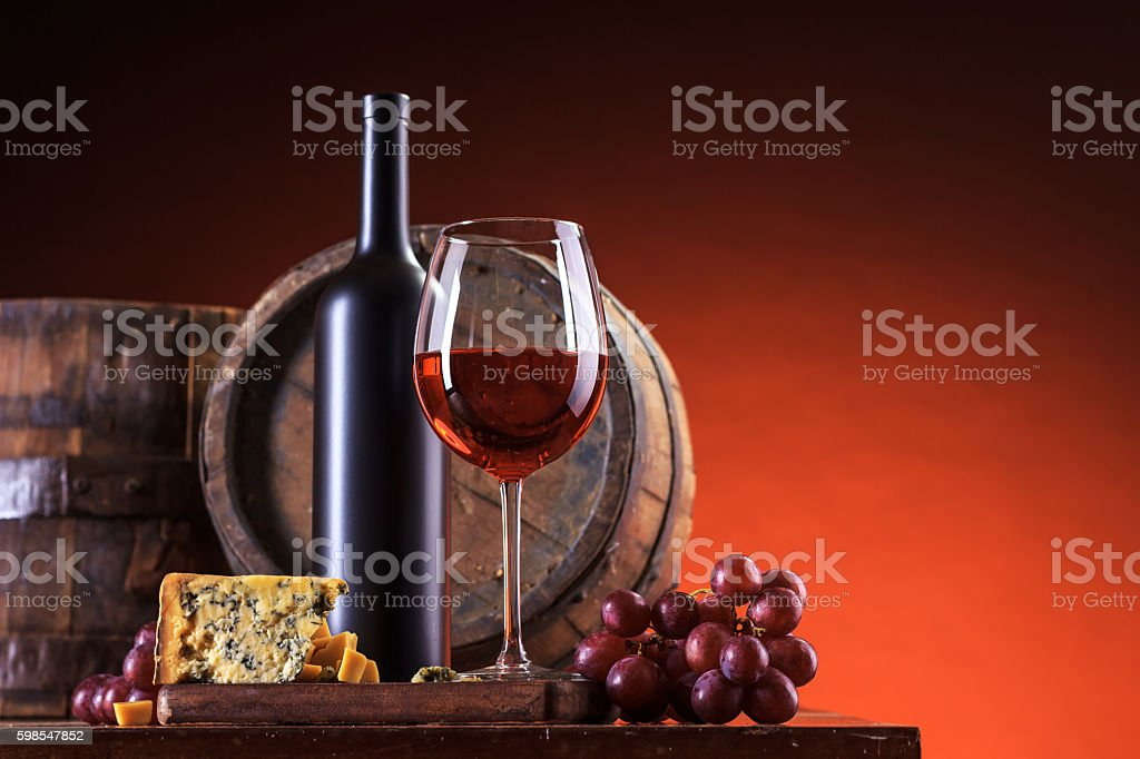 Glass and bottle of red wine with cheese and grape stock photo
