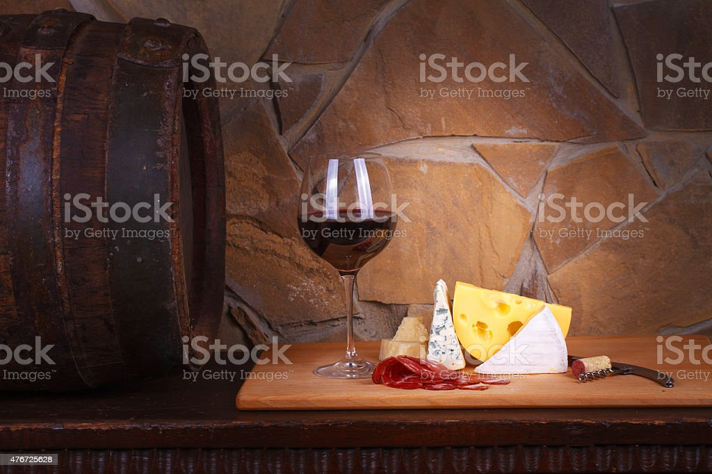 Glass and bottle of wine, cheese and prosciutto. Still life stock photo