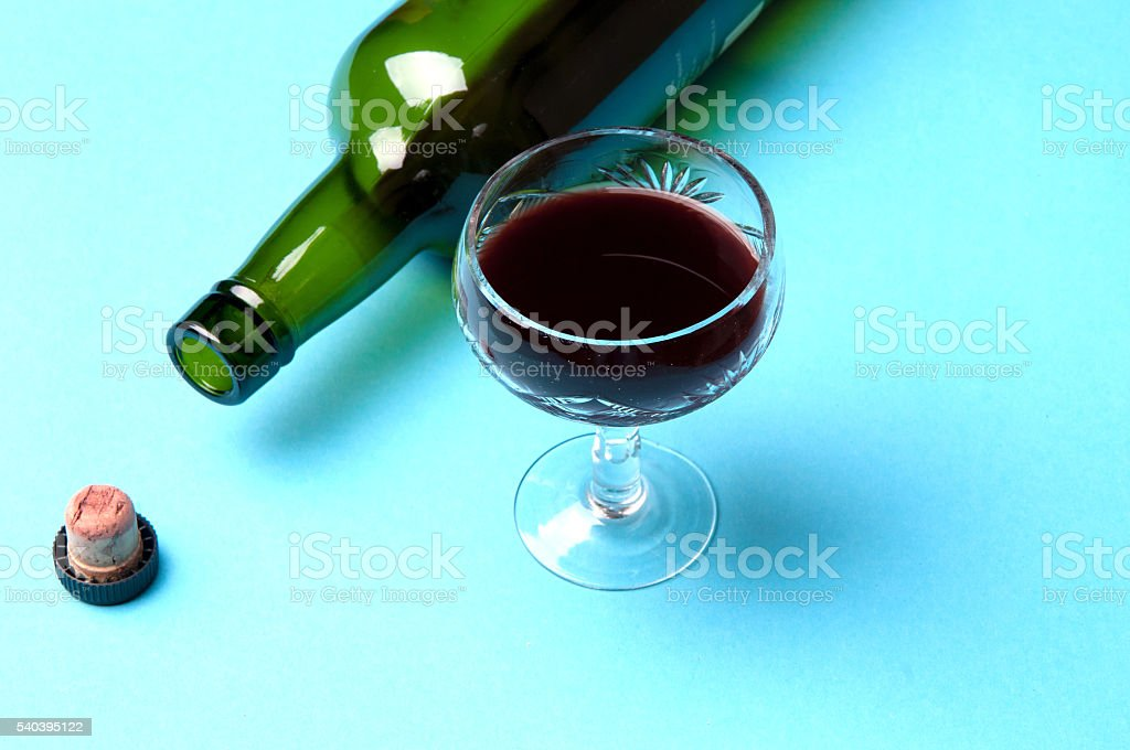 glass and bottle of wine isolated on a blue background stock photo