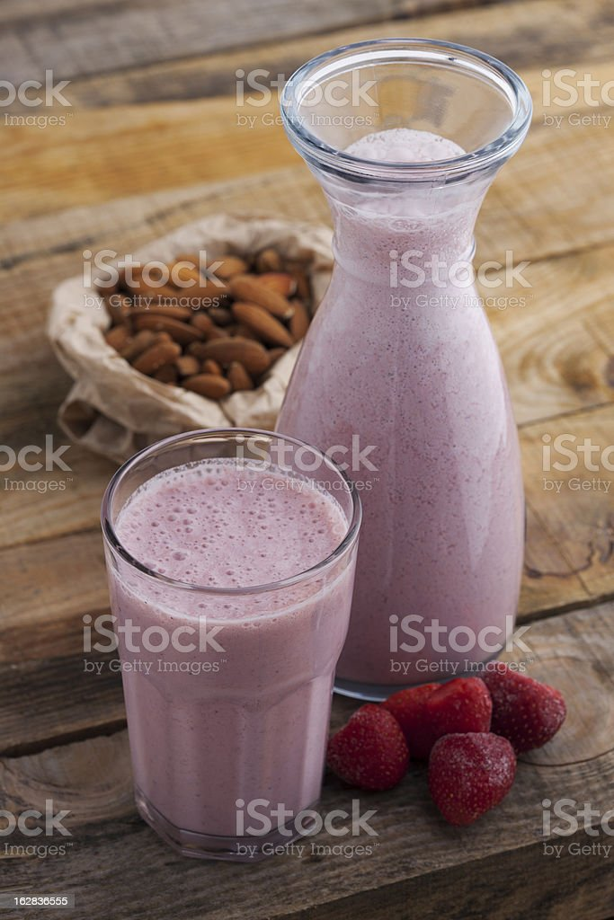 Glass and carafe of a strawberry almond smoothie royalty-free stock photo