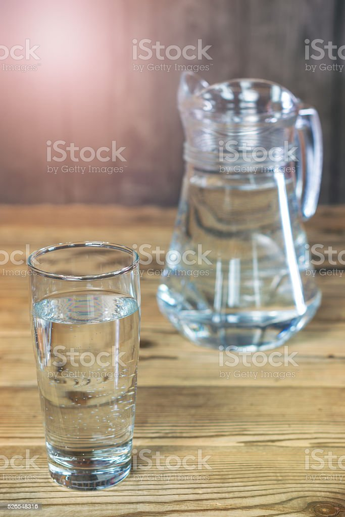 Glass and carafe of the purest water on wooden table stock photo