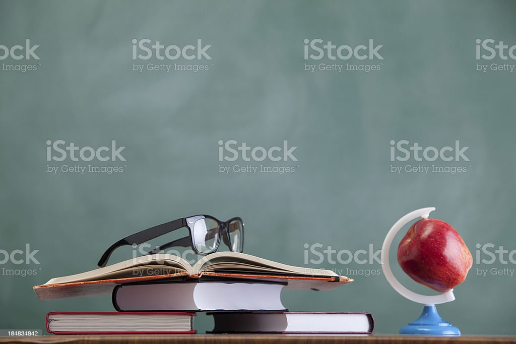 Glass, apple and stack of books before blackboard royalty-free stock photo