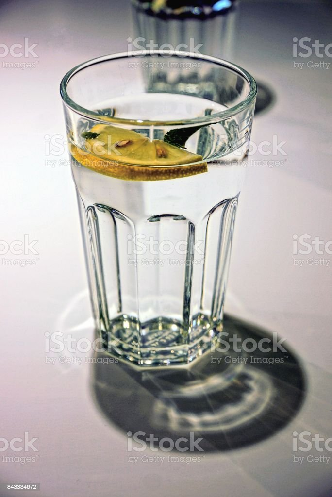 glass beaker with water and a slice of lemon stock photo