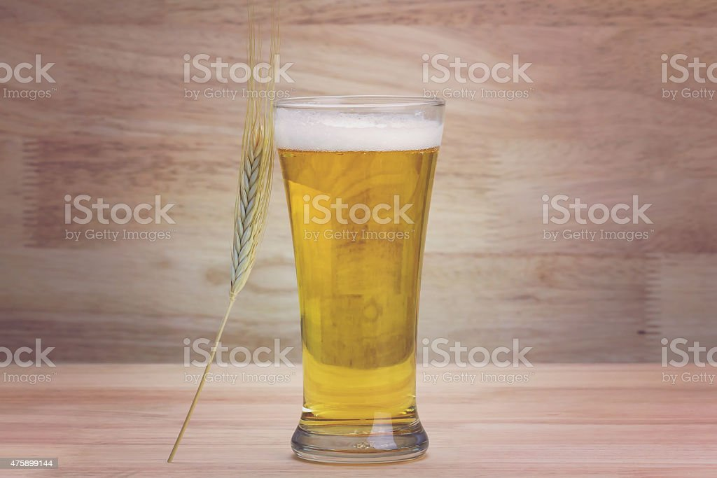 Glass beer and bale on wood background royalty-free stock photo