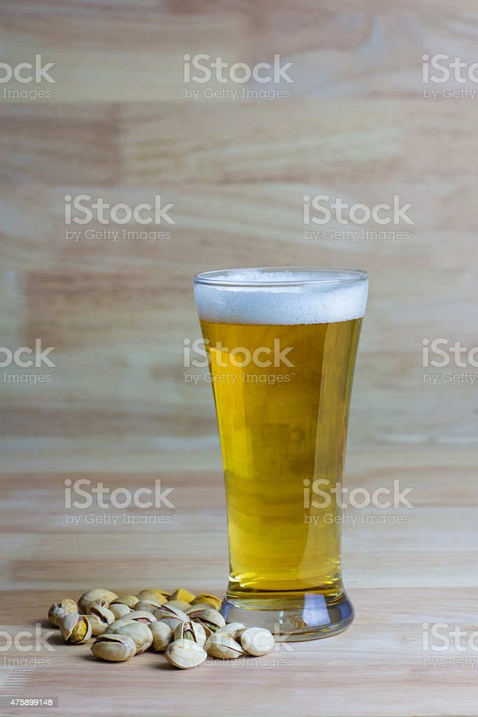 Glass beer and pistachios on wood background royalty-free stock photo