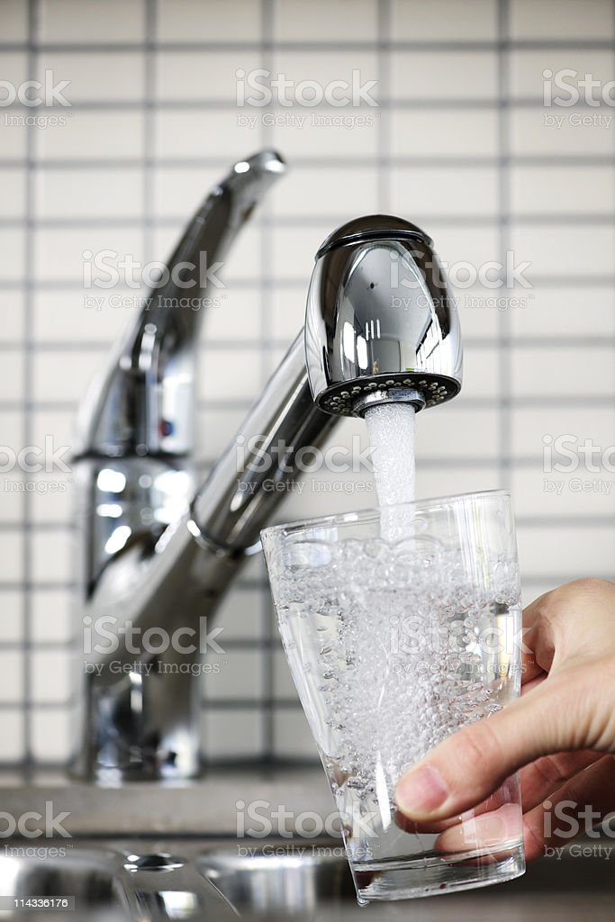 Glass being filled under a kitchen faucet with tap water royalty-free stock photo