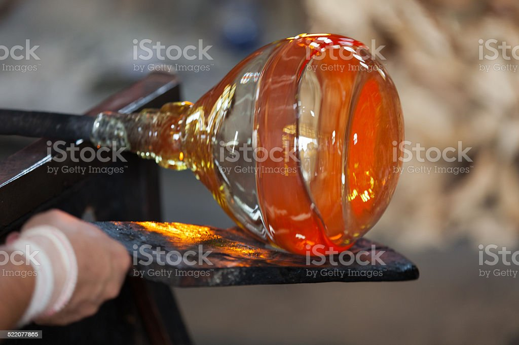 glass blower carefully making his product stock photo