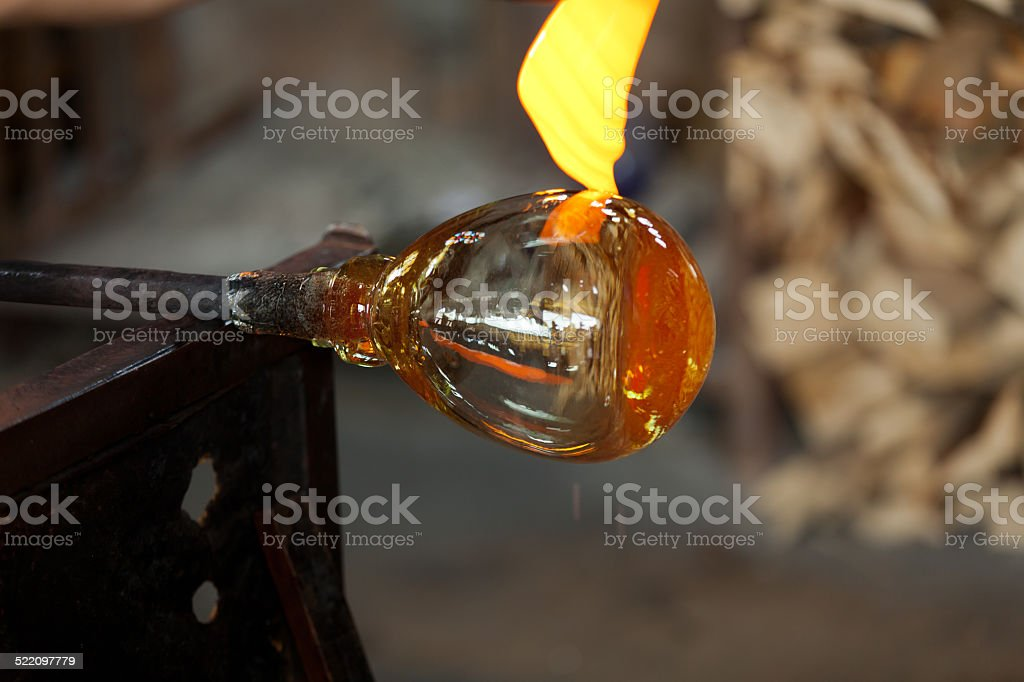 glass blower carefully making his product . stock photo