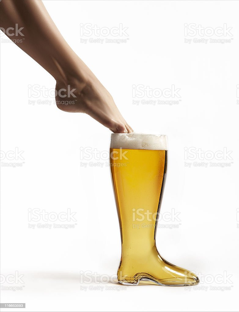 Glass boot with beer and foot stock photo