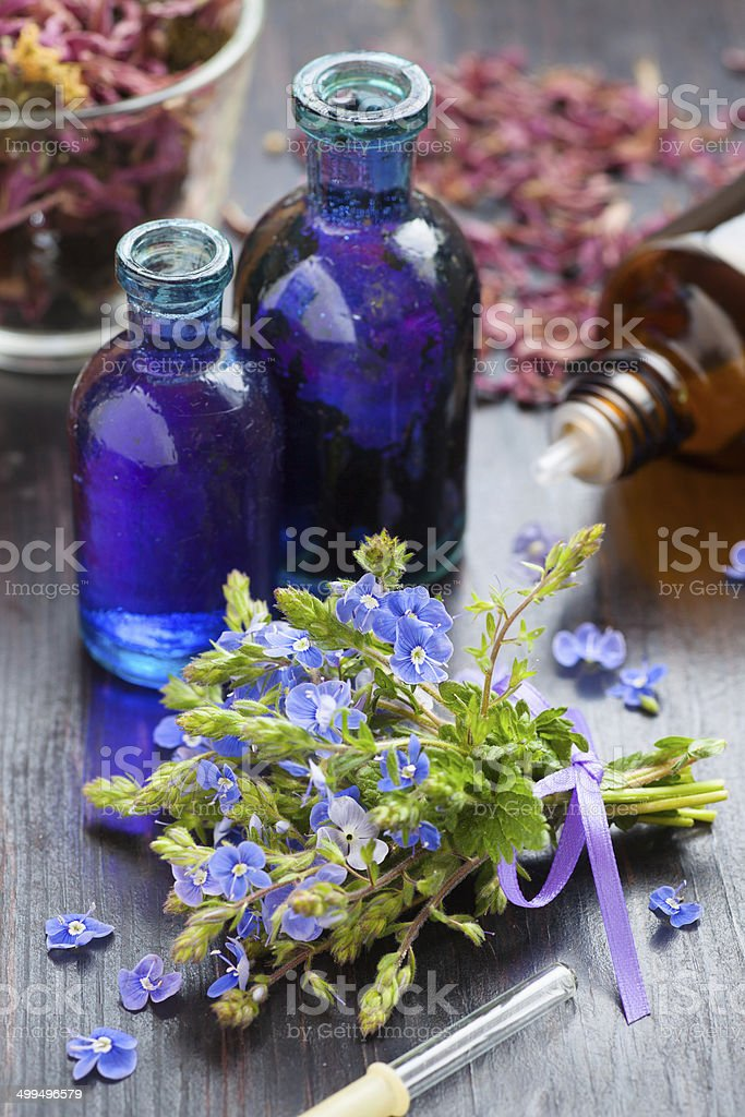 glass bottle of essential oil and blue healing flowers stock photo
