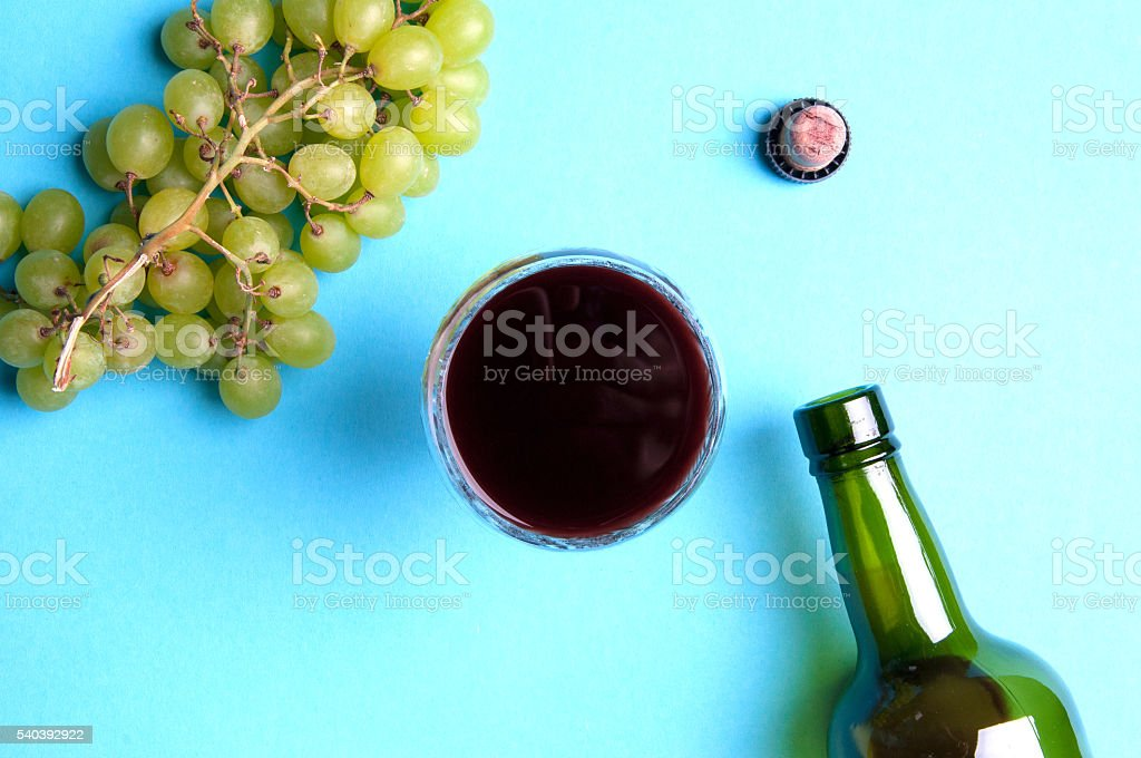Glass, bottle of wine, green grapes on a blue background stock photo