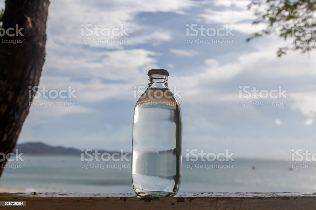 glass bottle on the beach stock photo
