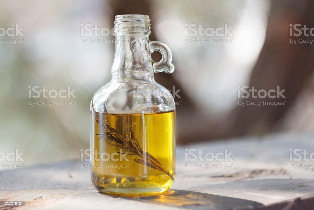 Glass bottle with homemade olive oil and sprig of rosemary stock photo