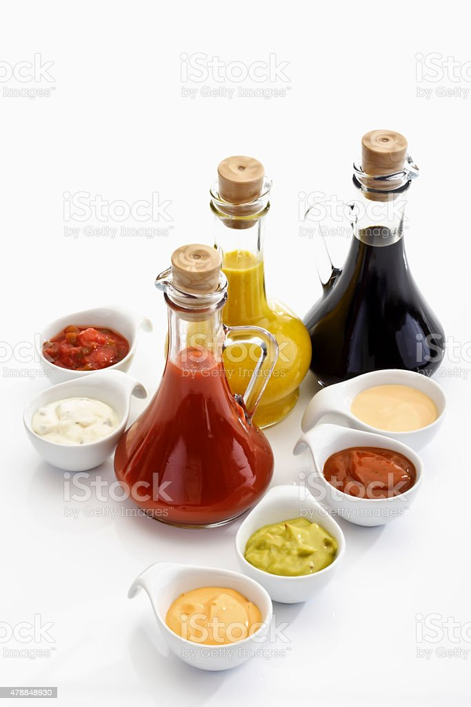Glass bottles and bowls with different sauces stock photo