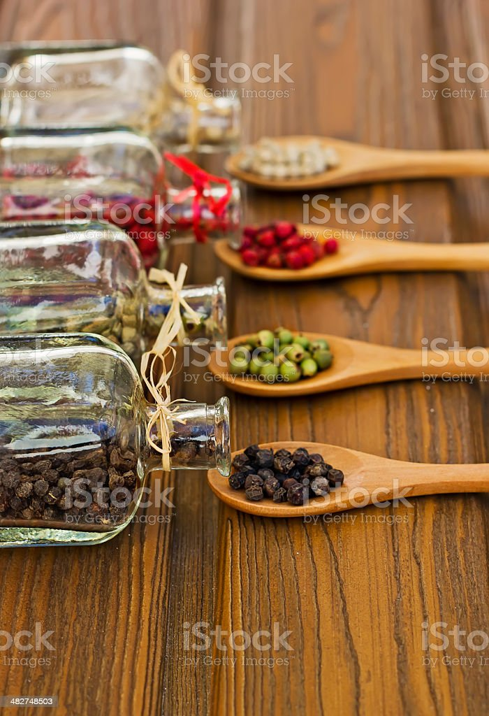 Glass bottles with four-color peppers royalty-free stock photo