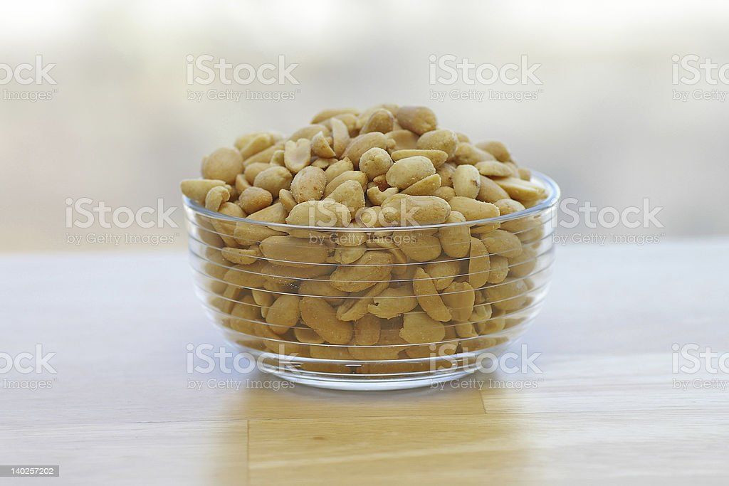 A glass bowl full of peanuts on a wooden board royalty-free stock photo
