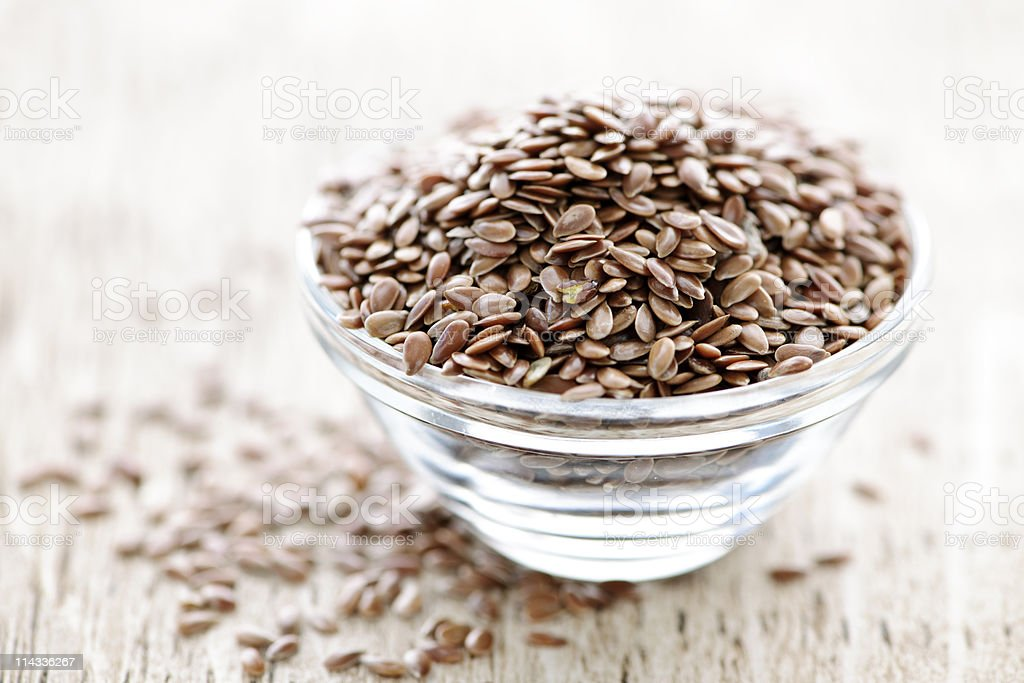 A glass bowl of brown flax seed stock photo