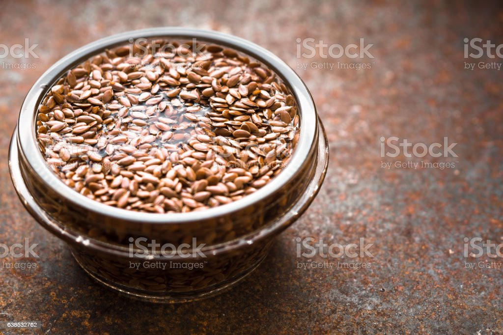 Glass bowl with flax seeds in the water  horizontal stock photo