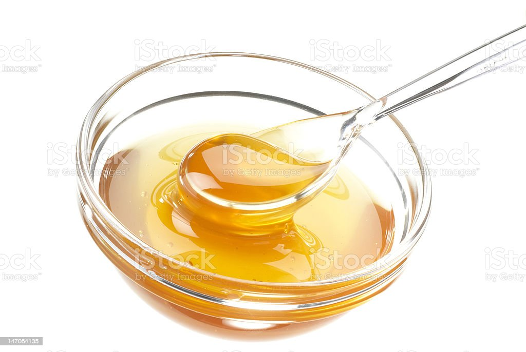 glass bowl with honey and a transparent spoon stock photo