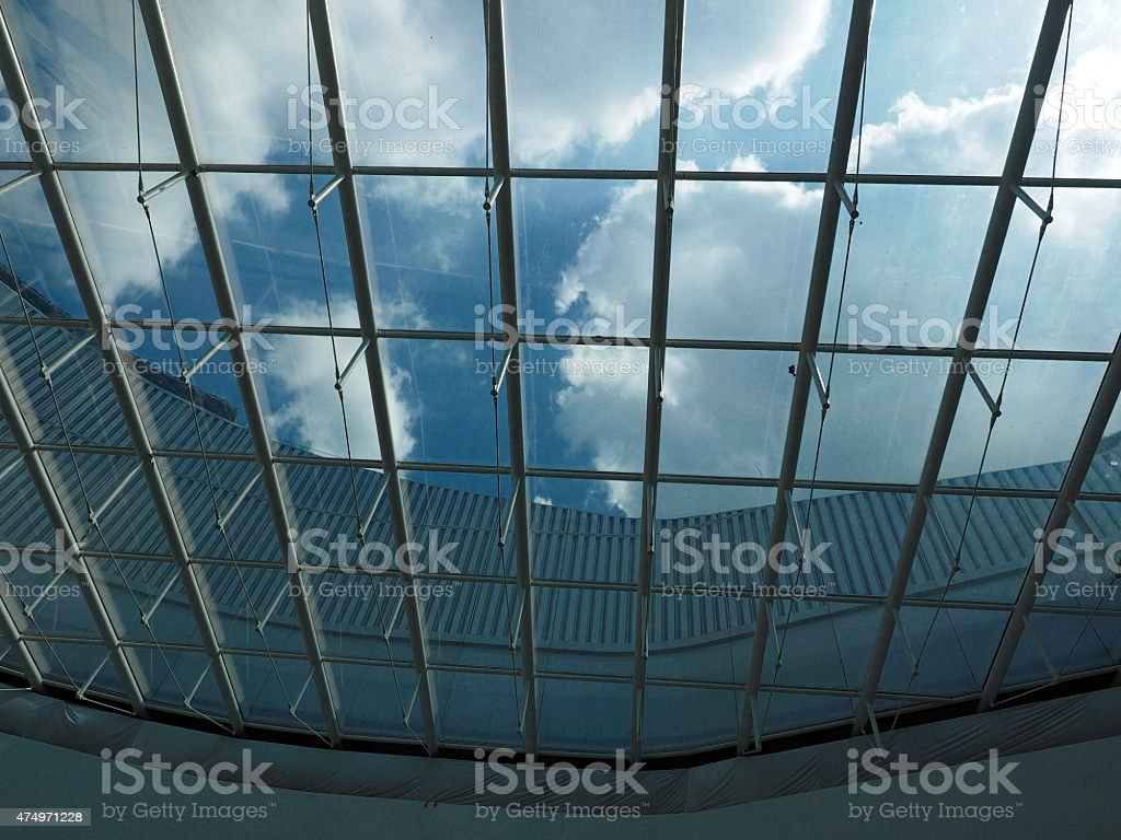 glass ceiling and cloudy blue sky stock photo