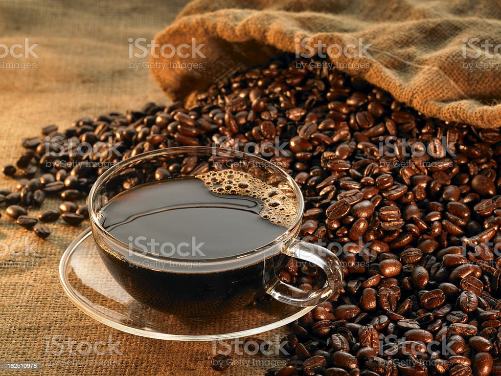 Glass coffee cup with beans on warm background royalty-free stock photo