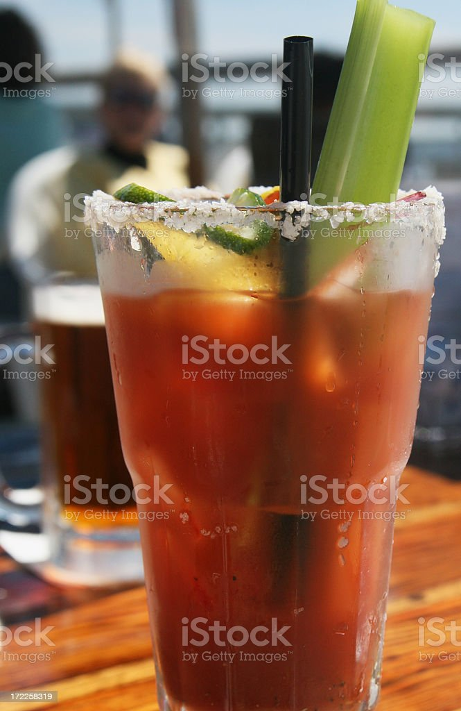 Glass contains bloody mary garnished with lime, salt and celery stock photo