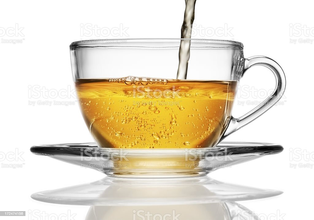 Glass cup of herbal tea being poured with bubbles stock photo