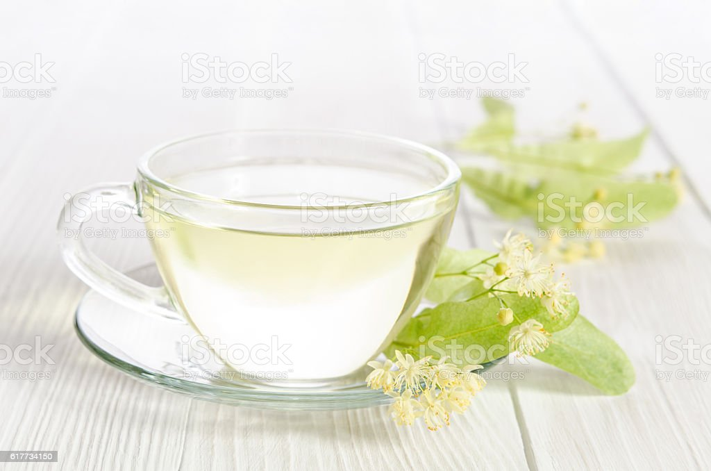 Glass cup of tea with linden on white wooden table stock photo