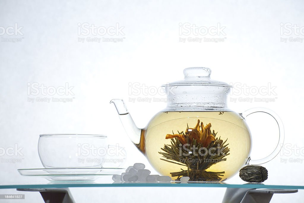 Glass cup on saucer, transparent teapot with Chinese blooming tea stock photo