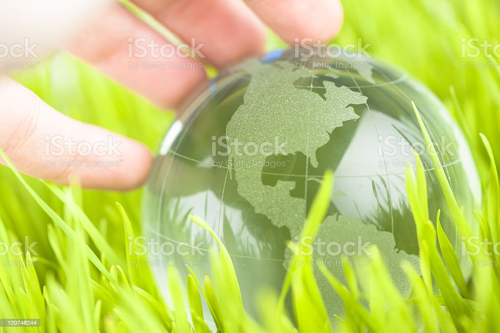 Glass earth in grass with hand royalty-free stock photo
