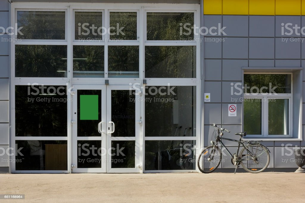 Glass entrance to office. Park zone of the megalopolis. Autumn trees are reflected in windows. Lonely bicycle. stock photo