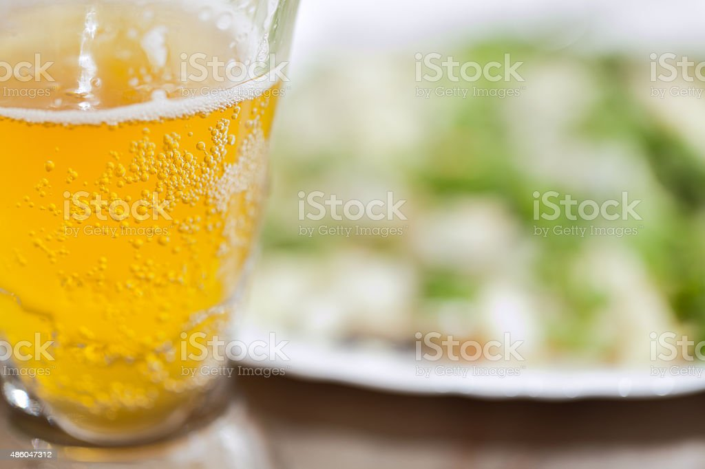 Glass filled with cloudy wheat beer with snacks stock photo