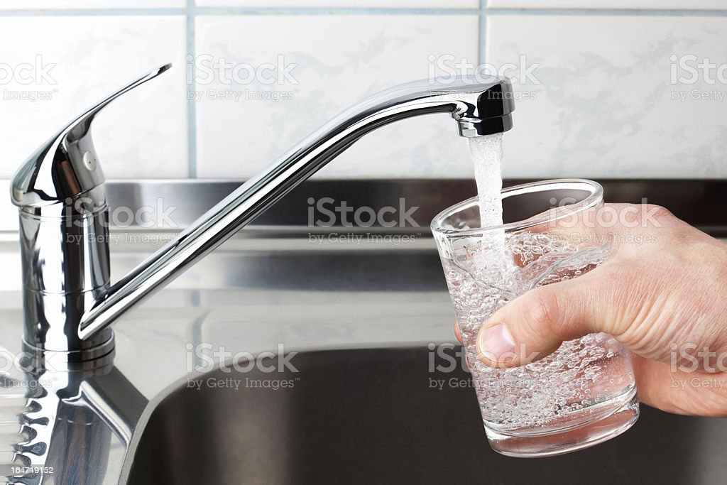 Glass filled with drinking water from kitchen faucet. stock photo