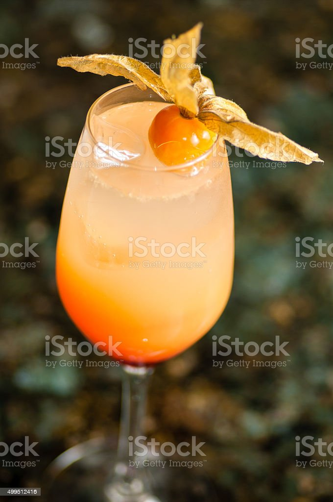 glass filled with orange colored cocktail stock photo