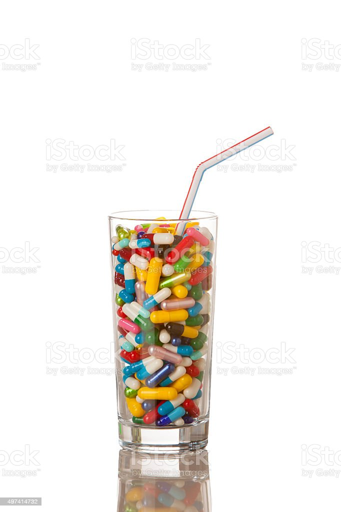 Glass filled with various capsules and pills. stock photo