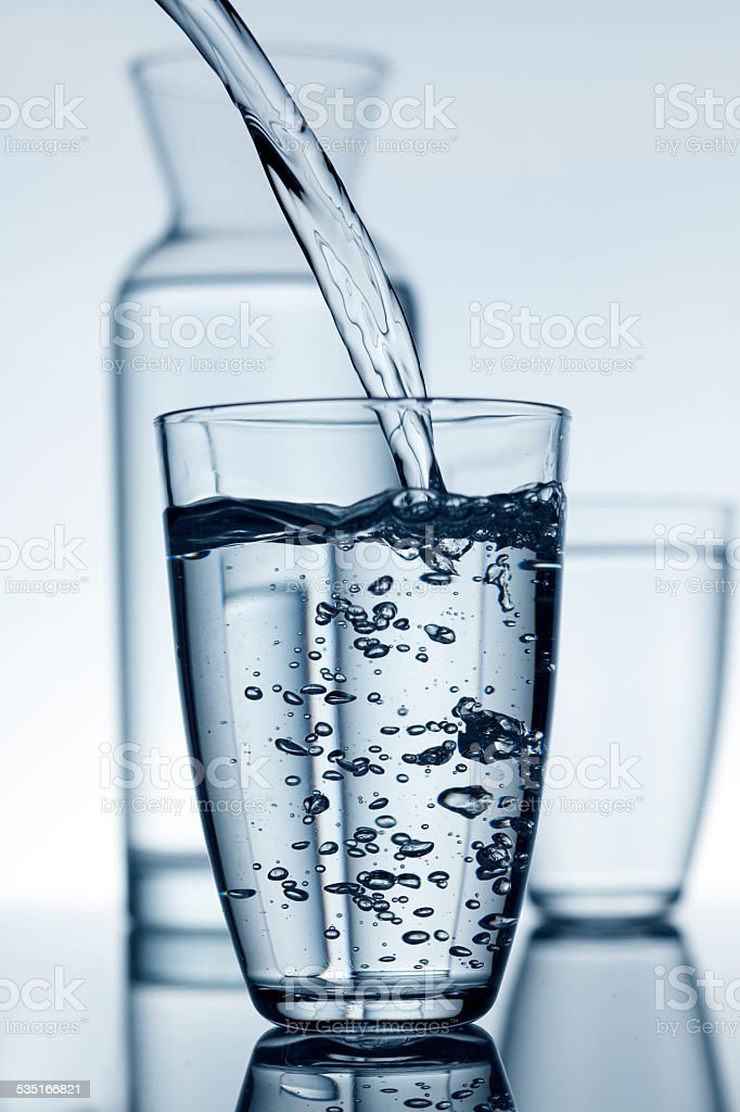 Glass filled with water and a carafe in the background stock photo