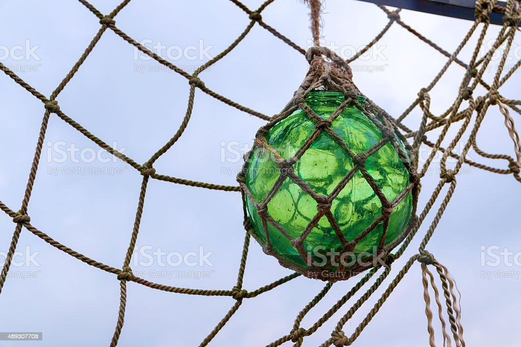 glass fishing float ball hanging in a net stock photo