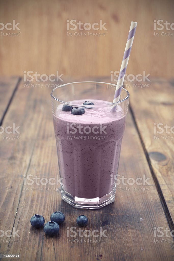 Glass full of blueberry smoothie with straw and blueberries stock photo