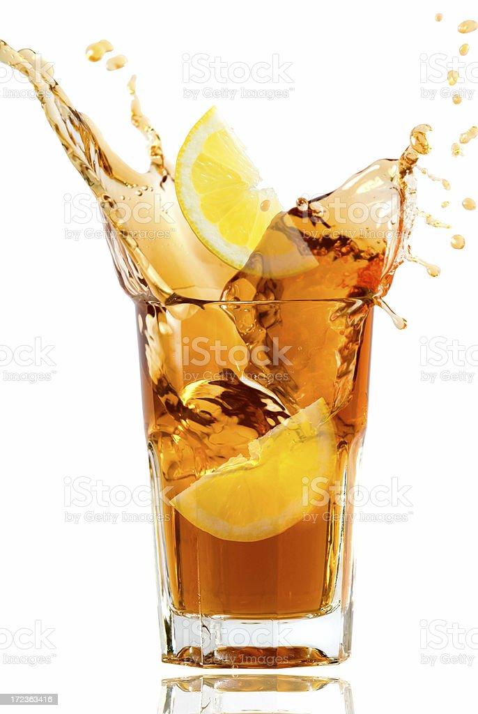 Glass full of fresh iced tea with lemon in artistic splash stock photo
