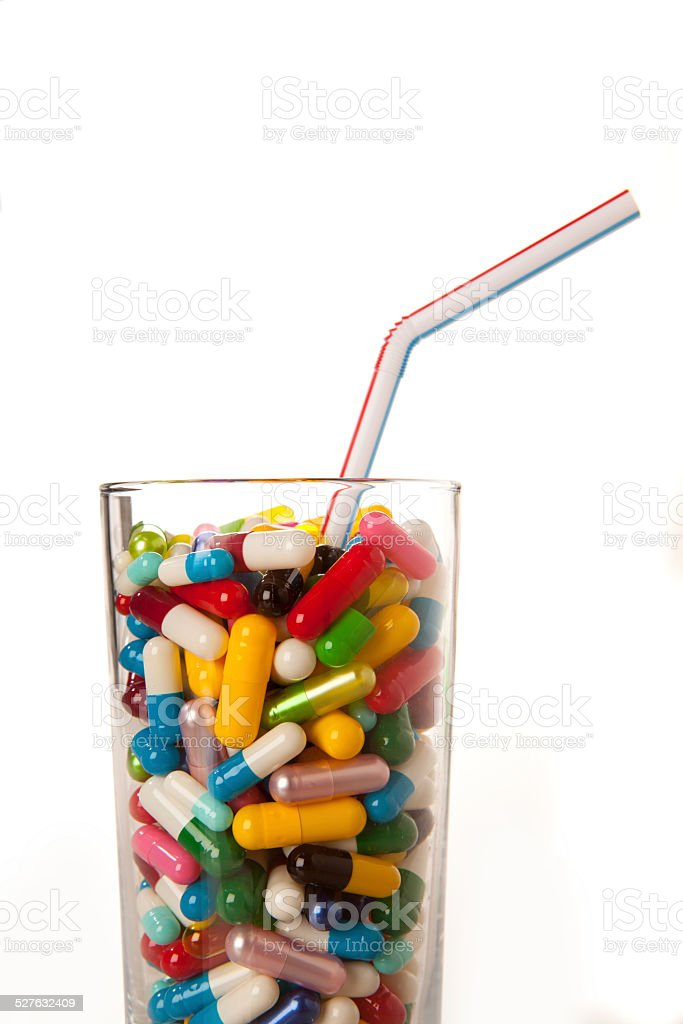 Glass full of vitamins and other pharmaceuticals stock photo
