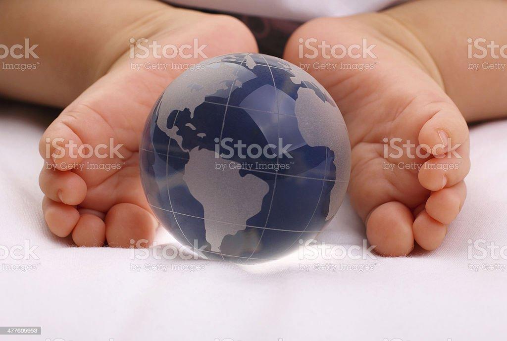 Glass globe and baby feet stock photo