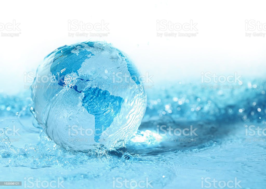 Glass globe being rolled in water stock photo