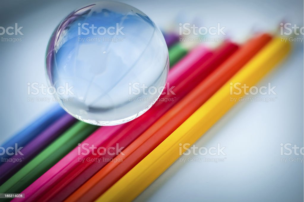 Glass globe lying and colored pencils royalty-free stock photo