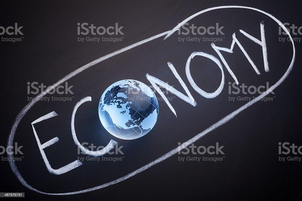 Glass Globe on Blackboard - Economy Blue Environmental Conservation stock photo
