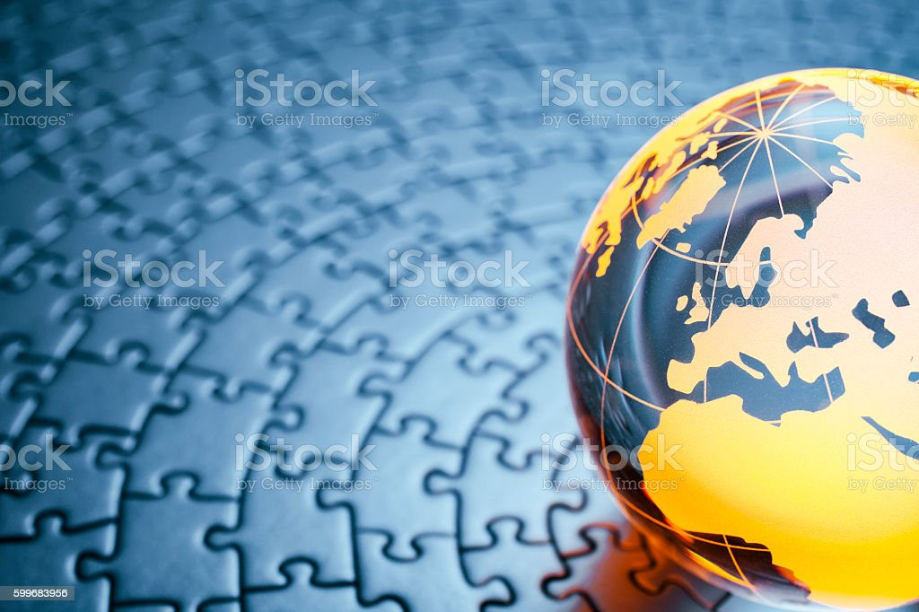 Glass globe on circular jigsaw puzzle stock photo