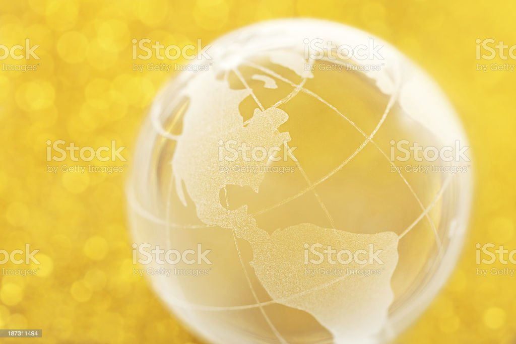 Glass globe on golden background stock photo
