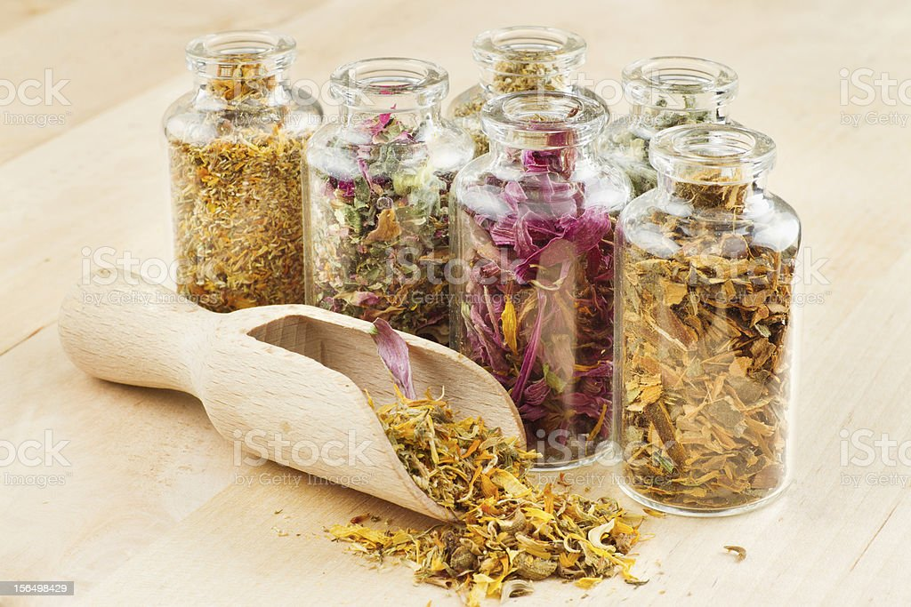 Glass herb jars on a wooden table with wooden scoop royalty-free stock photo