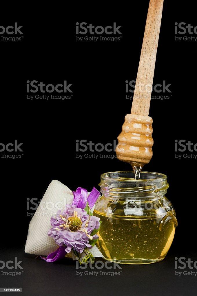 Glass honey with sticks stock photo